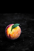 A peach with a leaf on a dark background