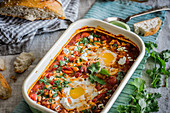 Tomato stew with poached eggs, chickpeas and parsley