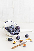 Damsons in a colander with a knife on a light surface