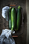 Three courgettes in a wire basket