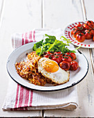 Latkas with a fried egg and roasted tomatoes
