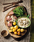 Venison steak with a brandy-mushroom sauce, roast potatoes and green beans
