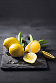 Lemons, whole and sliced, on a chopping board