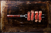 Slices of grilled meat barbecue steak, Rib eye on meat fork on dark metal background