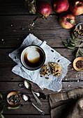 Gebäck neben leergetrunkener Tasse Kaffee auf rustikalem Holztisch