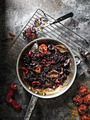 Rustic pan filled with black, squid ink pasta and roasted tomatoes on a dark rustic surface