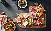 An antipasti plater with focaccia, pickled chillis, grissini, Prosciutto, olives, gorgonzola, salami, sopressa and grilled courgettes
