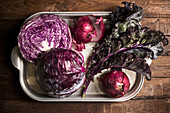 A tray full of red and purple vegetables in a moody lighting and adtmosphere