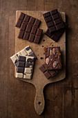 Multiple types of chocolate laid out on a rustic wooden cutting board