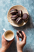 Young female having a cup of coffee and chocolate cookies for breakfast