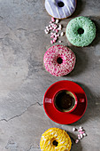 Variety of colorful glazed donuts with pink sugar and red cup of black coffee