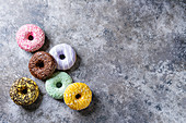 Variety of colorful glazed donuts over gray texture background