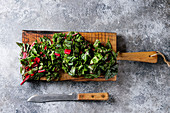 Cutting fresh chard mangold salad on wooden chopping board with knife over gray texture background