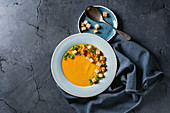 Plate of vegetarian pumpkin carrot soup served with croutons and onion on textile napkin
