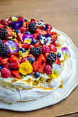 Pavlova with whipped cream, berries, passion fruit and edible flowers