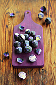 Fresh Brussels sprouts on a purple chopping board