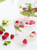 Water flavoured with raspberries, mint and ice cube