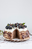 A pancake cake with chocolate and blackberries