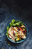 A salad bowl with grilled chicken breast, vegetables and barley