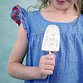 A little girl holding a banana and stacciatella ice cream stick