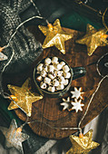 Hot chocolate with marshmallows and gingerbread cookies over rustic wooden board