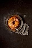 Kürbis-Napfkuchen auf dunklem Untergrund (Aufsicht)