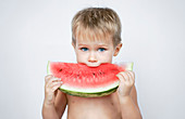 A young blonde boy biting into a slice of watermelon