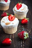 Erdbeer-Baiser-Cupcakes auf Holzuntergrund
