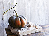 A nutmeg pumpkin on a wooden board with a cloth and a knife