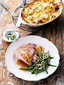 Zickleinkeule in Honig-Rosmarin-Jus mit Kartoffelgratin und Bohnen