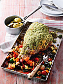 A leg of lamb with a herb crust, herb potatoes and oven-roasted vegetables