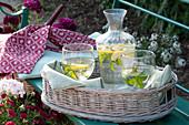 Korbtablett mit Zitronen-Minze Wasser in Flasche und Gläsern auf Bank
