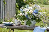 Blau-weißer Strauß in Suppenterrine auf Gartenbank :