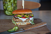 A chicken burger with gherkins