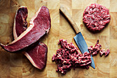 Beef steaks, minced meat and a beef patty with a knife on a chopping board