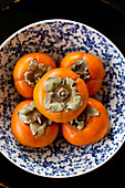 Five persimmons in a bowl