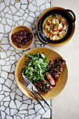 Beef with arugula, dumplings and shrimps on a mosaic table