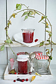 Cornelian jam in storage jars under a cornel cherry branch