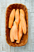 Peeled sweet potatoes in a wooden dish