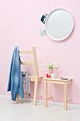 Garderobe und Ablage aus zersägtem Stuhl an rosafarbener Wand