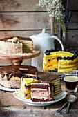 Drei verschiedene Kuchen: Leningrad-Kuchen, Schokoladen-Käsekuchen und Vanillekuchen mit Beeren
