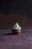 A chocolate cupcake with pistachio cream, sugar stars and edible glitter (vegan)