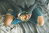 Healthy winter breakfast in bed: Woman in sweater and jeans holding rice coconut porridge with figs, berries, hazelnuts