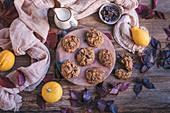 Pumpkin chocolate chip cookies served on a ceramic plate on rustic wooden table