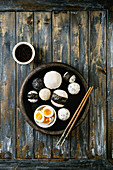 Stone tray with different size rice balls with black sesame and seaweed nori, served with soft boiled eggs, soy sauce