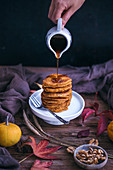 Woman pouring maple syrup on pumpkin pancakes served on a little cake stand on rustic wooden table