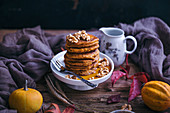Pumpkin pancakes topped with walnuts and maple syrup served on a little cake stand on rustic wooden table