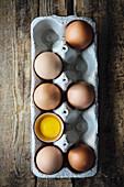 Ganze braune Eier und ein aufgeschlagenes Ei in Eierkarton (Aufsicht)