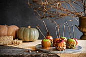 Marble tray of caramel apples with fall decor in the background