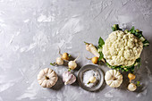 Variety of white vegetables raw organic cauliflower, pumpkins, garlic, parsnip and radish with plate of sea salt over gray texture background